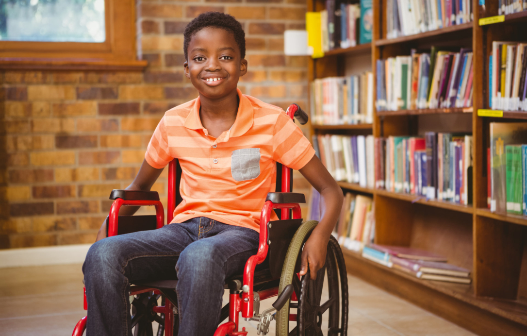 disabled young boy in wheelchair smiling