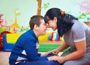 a cheerful caregiver and a boy with disability